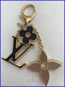 Authentic Louis Vuitton key ring in gold type hardware, black enamel and taupe e